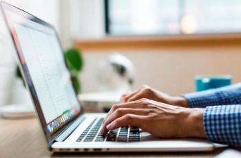 Imagem mostra uma pessoa mexendo no computador em alusão ao teletrabalho