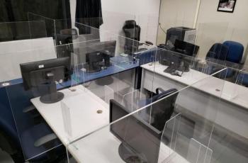 Imagem mostra sala de audiência com divisórias de acrílico
